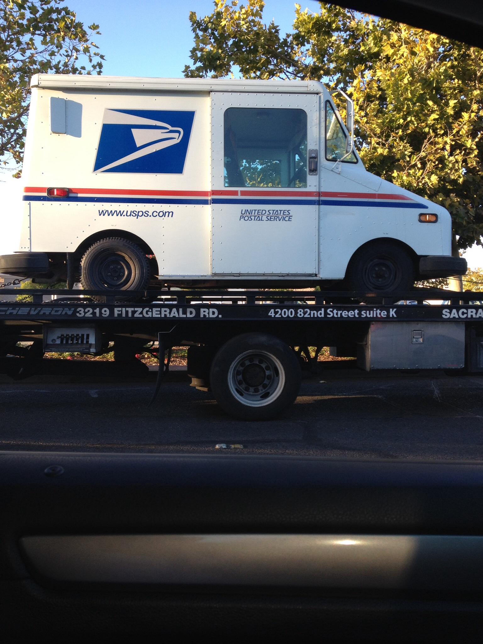 Postauto auf Abschleppwagen