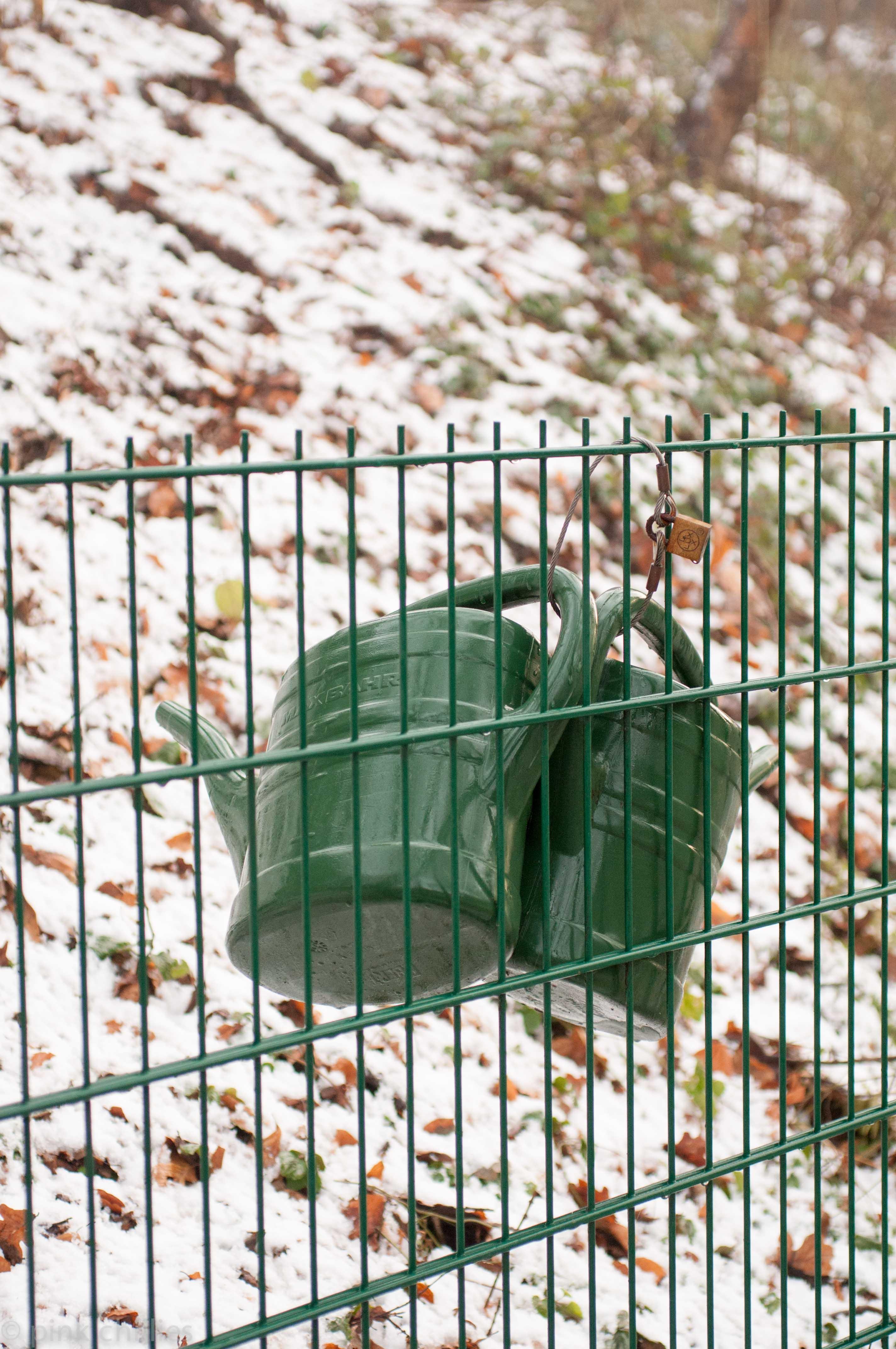 Gießkannen am Zaun