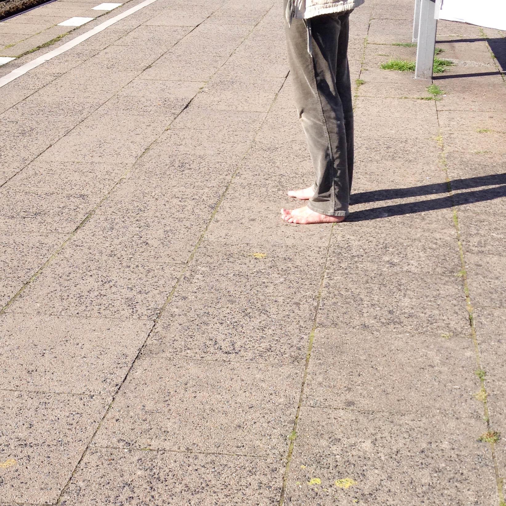 barfuss auf Bahnsteig