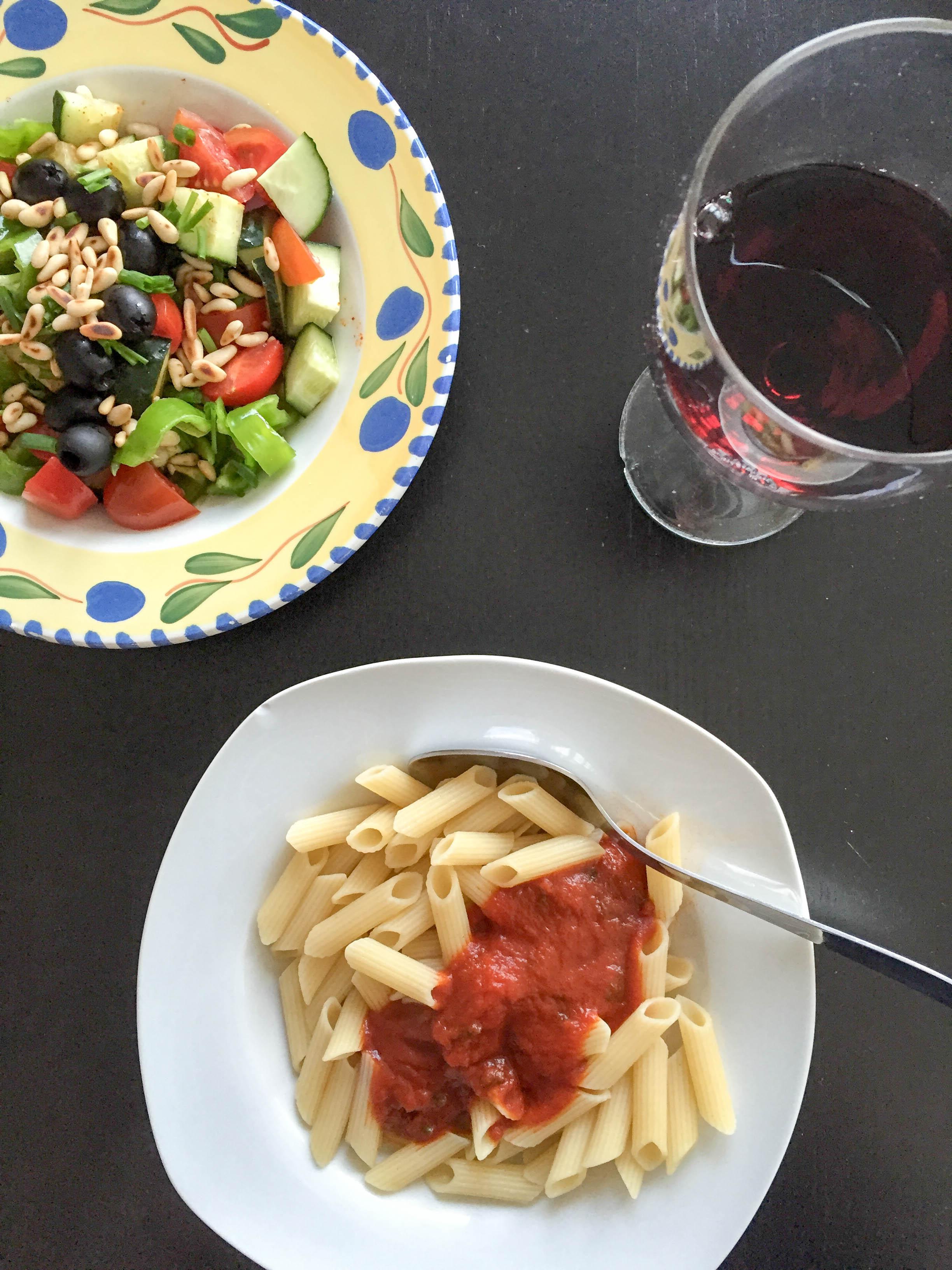 Abendessen Pasta mit Salat und Rotwein