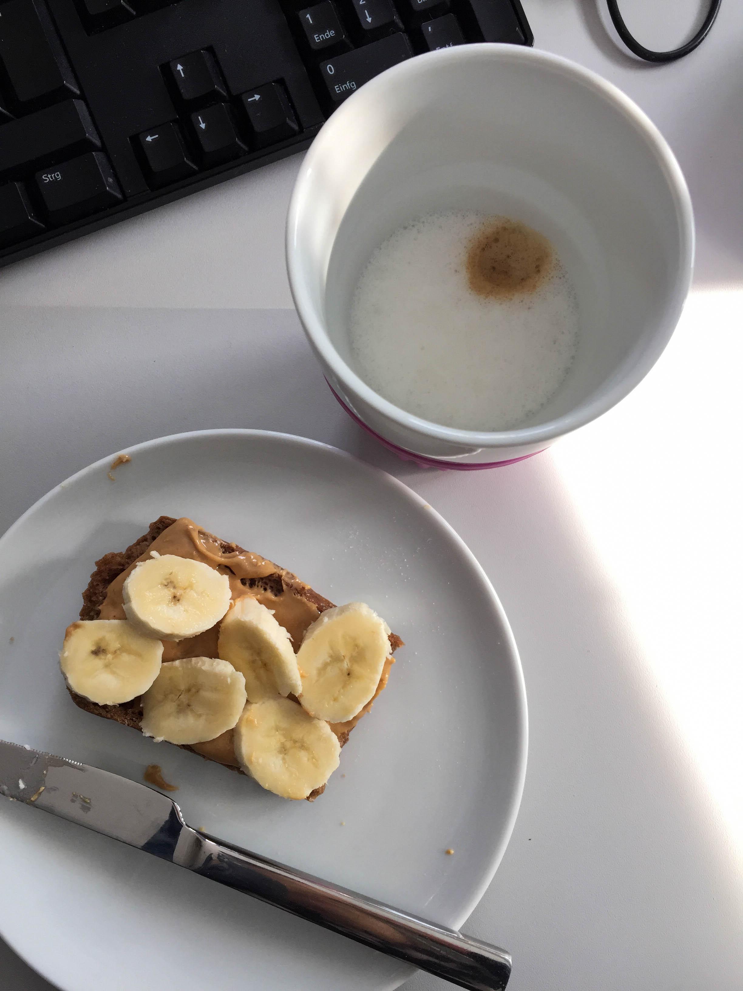 Bürofrühstück - Kaffee mit Mandelmilch, dazu ein Toast mit Cashewbutter und Banane.