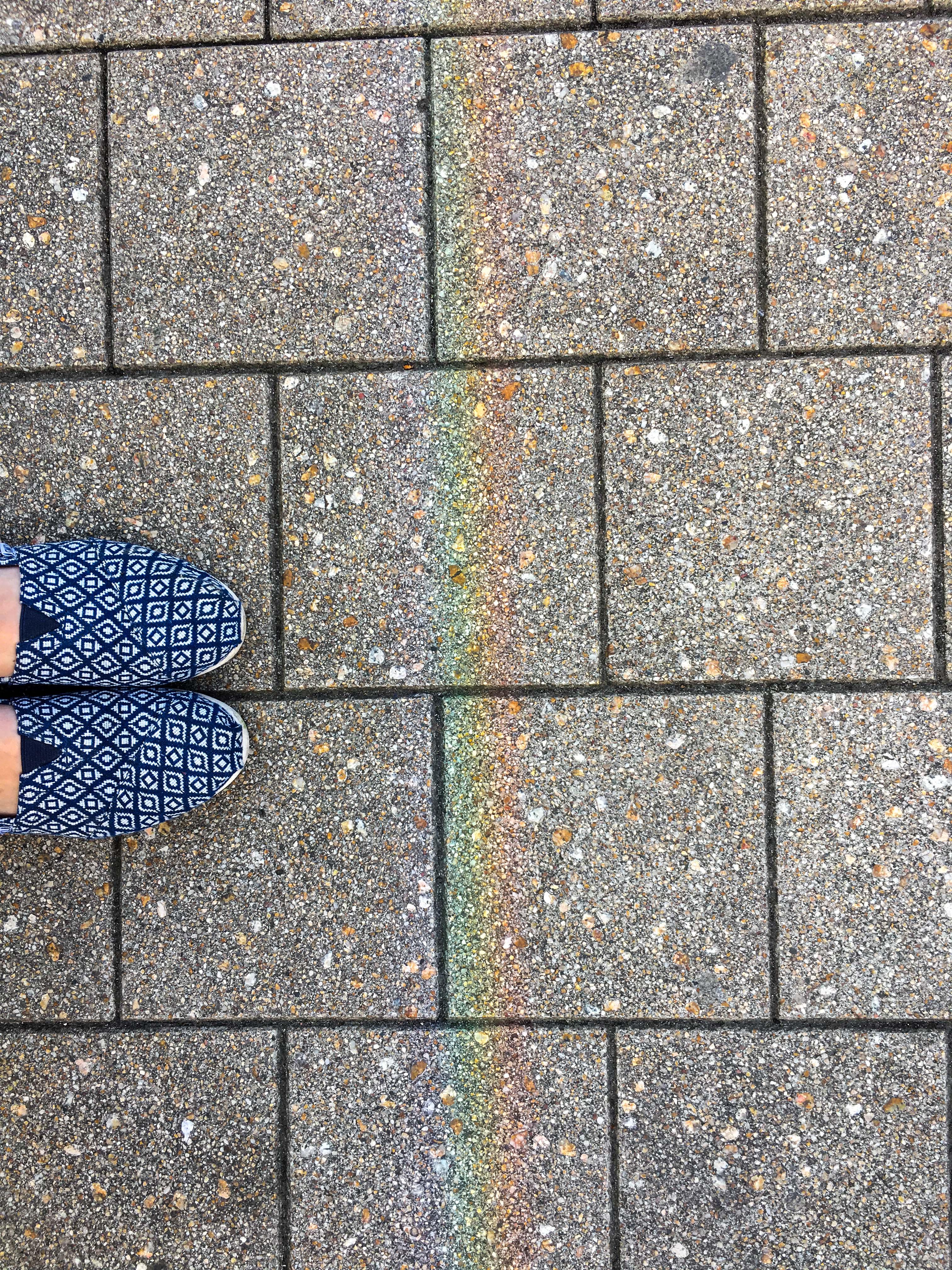 Regenbogen auf Gehweg