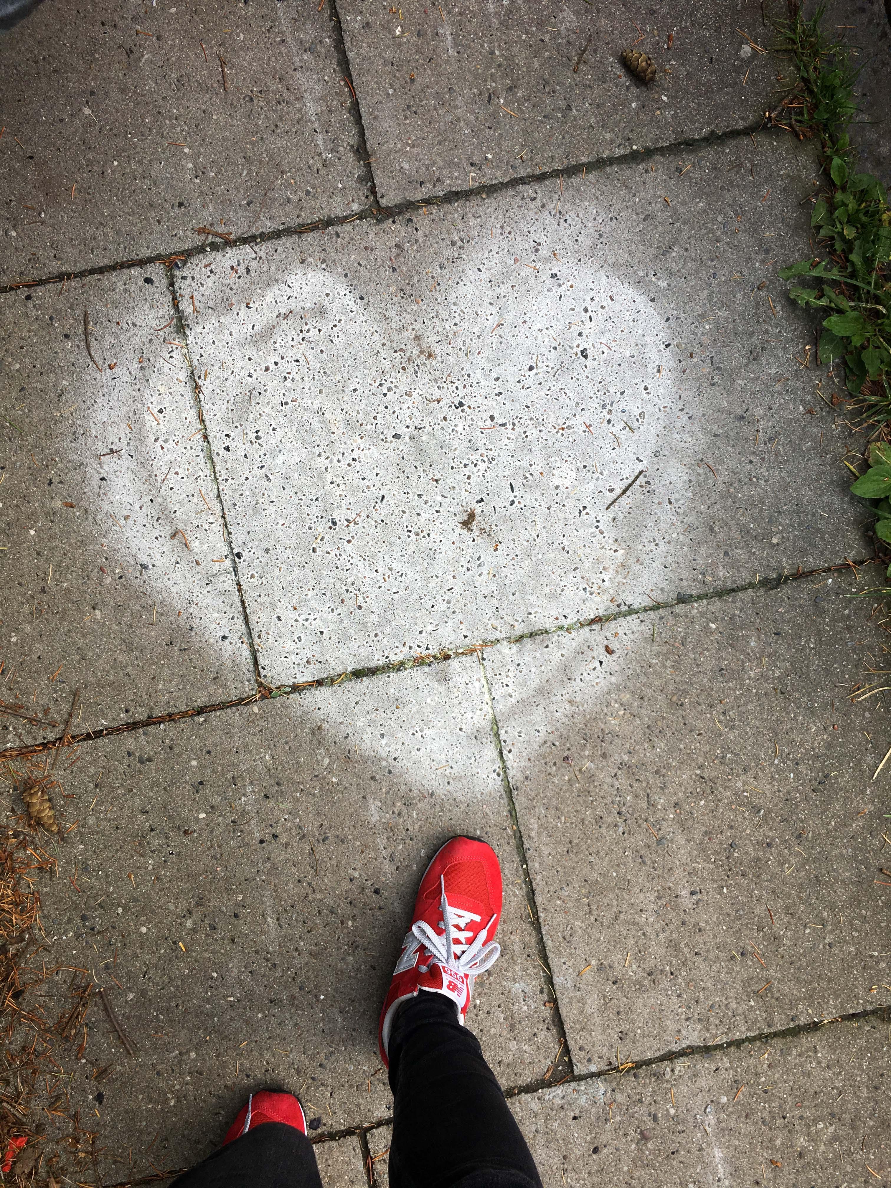 Herz auf Gehweg aufgemalt in weiß