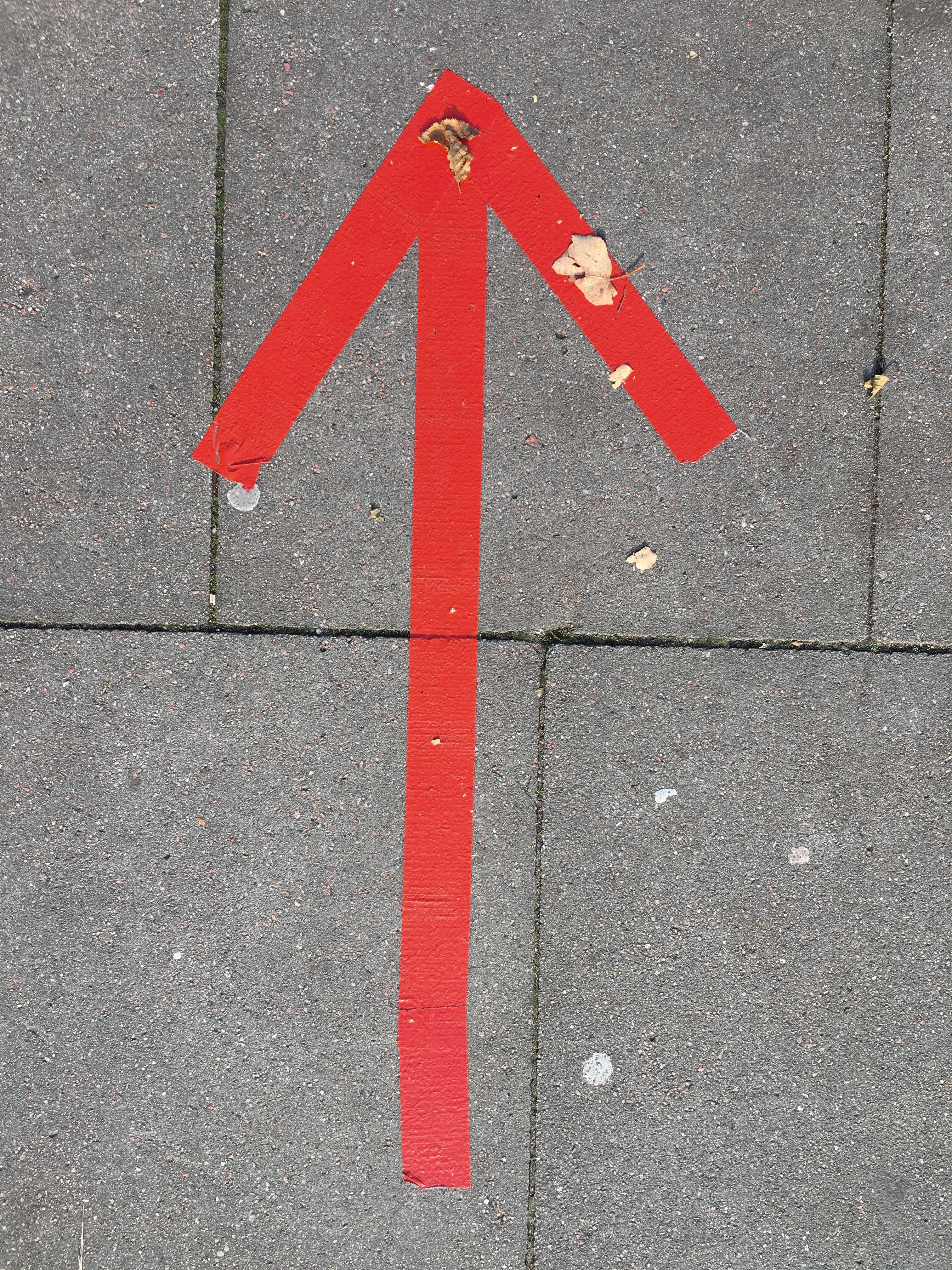 roter Pfeil auf Gehweg geklebt