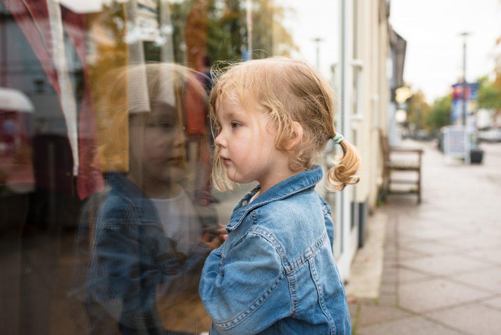 Kleinkind blickt in ein Schaufenster